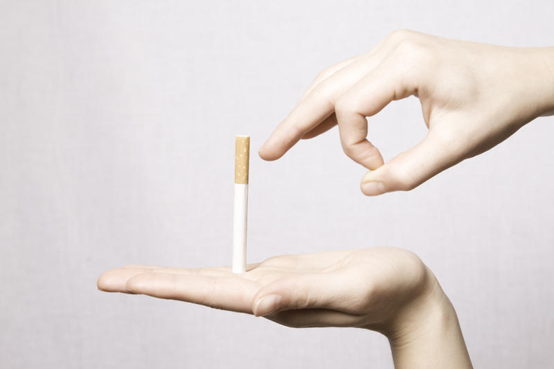 Mulher jogando o cigarro fora para prevenir as celulites