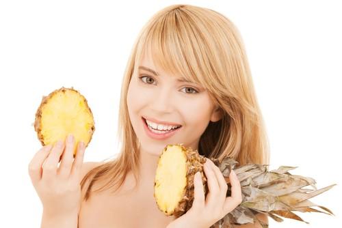 Mulher com dois pedaços de abacaxi nas mãos