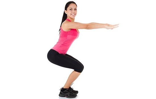Mulher agachada fazendo exercício de agachamento