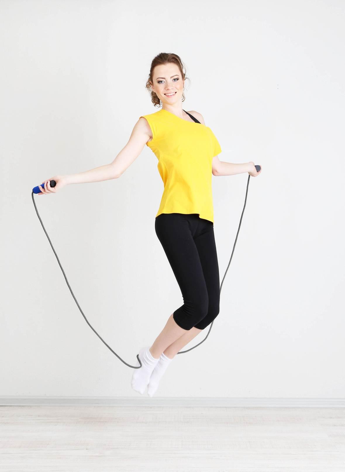 Mulher bonita pulando corda como exercício físico